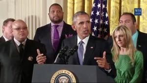 Barack Obama at White House lectern surrounded by people