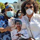 masked health workers holding photo of colleague