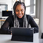 Woman smiling in front of laptop computer