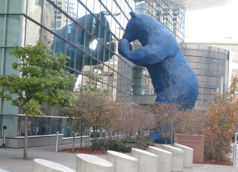 blue bear statue peering into Denver Convention Center