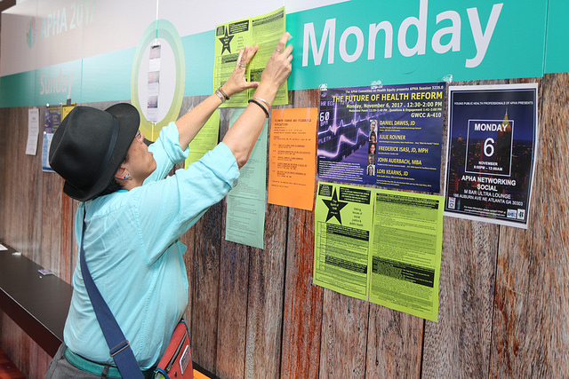 person in hat placing sign on bulletin board