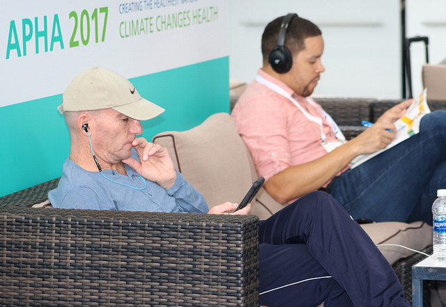 men reading Annual Meeting program while seated on couch