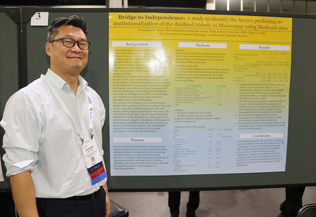 smiling man in front of Annual Meeting research poster