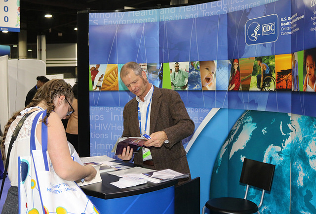 man and woman peruse publications at Expo booth