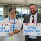 smiling man and woman holding Monday Mile signs