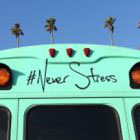 turquoise bus with #never stress and palm trees in background