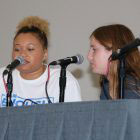 two teens at table in front of microphones